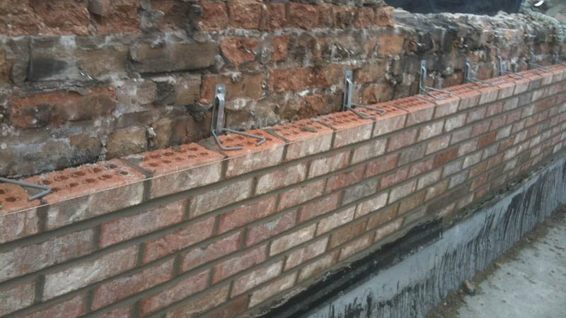 Brick masonry restoration completed on a wall by Amplify Masonry