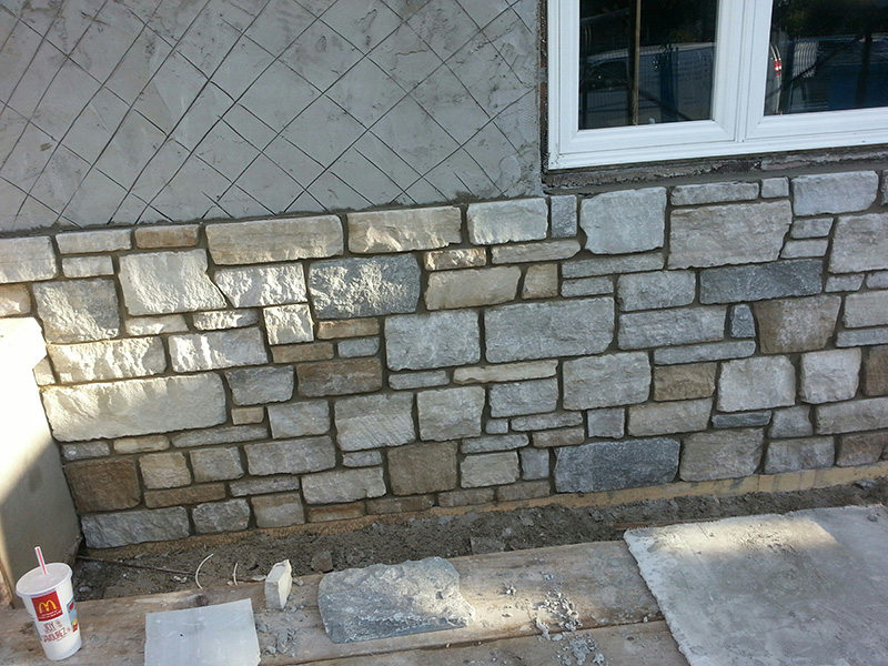 Natural stone brick veneer on a wall completed by Amplify Masonry