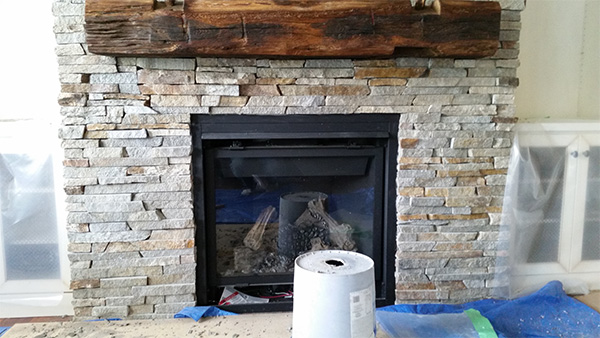 natural stone veneer put on a stone fireplace completed by Amplify Masonry